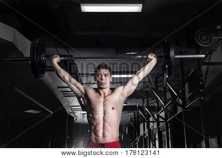 Musclular shirtless athlete deadlifts a barbell over his head in crossfit gym.Crossfit with weghts.