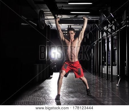 Powerful crossfit athlete in a over-head lunge with a heavy weight in a crossfit gym.