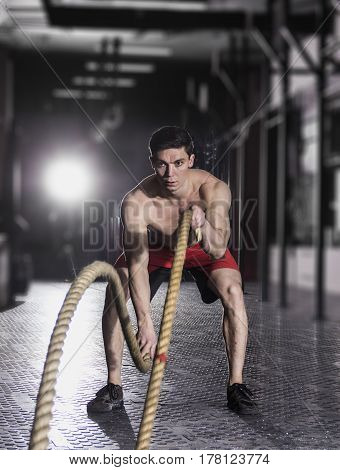 Concept: power, strength, healthy lifestyle, sport. Powerful attractive muscular man CrossFit trainer do battle workout with ropes at the gym
