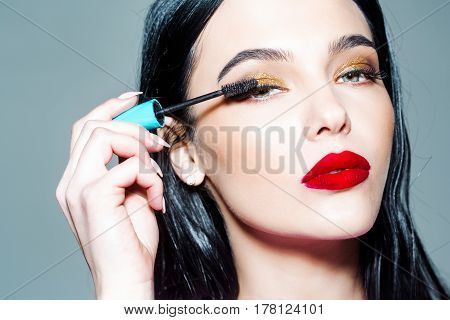 pretty woman or cute sexy girl with long curly brunette hair has red lips makeup on adorable face holds mascara brush near eyelashes on grey background