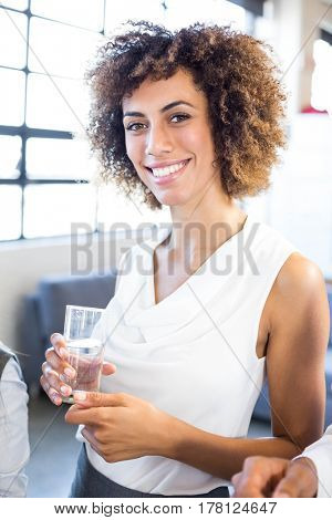 Portrait of businesswoman having a glass of water in office