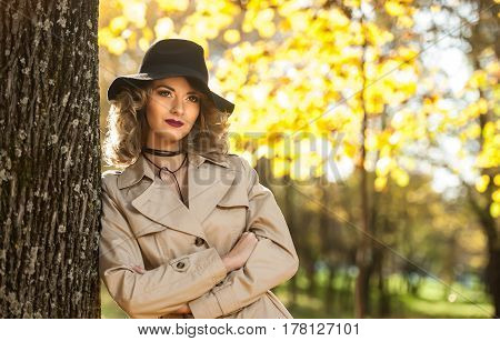 beautiful blonde woman with cream coat , long legs and black hat in a autumn scene .Portrait of a very beautiful young Elegant and sensual woman with curly hair posing in autumn park.