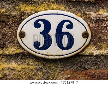 enameled old house number 36 in wihte and blue