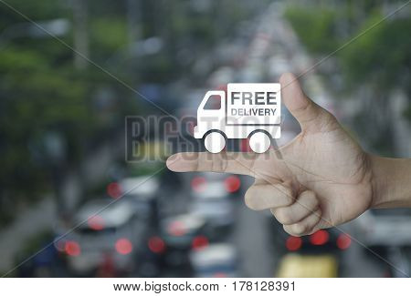 Free delivery truck icon on finger over blur of rush hour with cars and road Transportation business concept