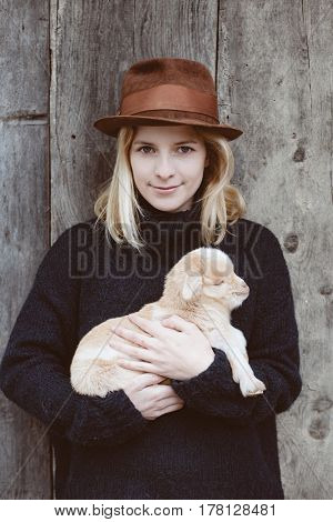 Farmer woman with baby goat. Livestock at farm.