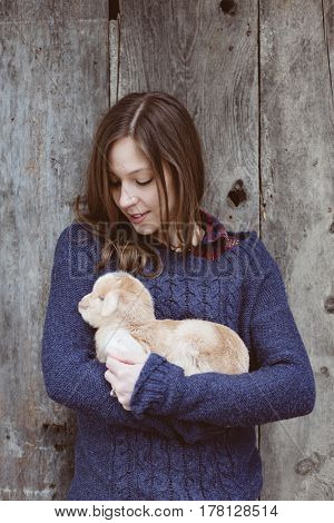Young woman with baby goat. Livestock at farm.