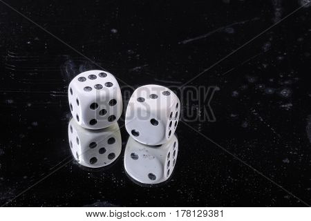 Old bone dice on damaged mirror background