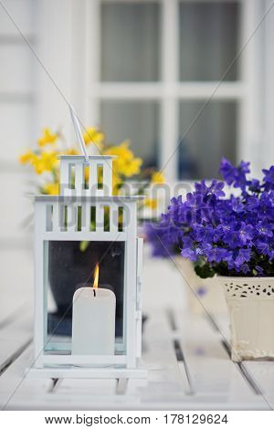 wedding candles on white wooden table and a purple flowers. Scantinavian style. Norway