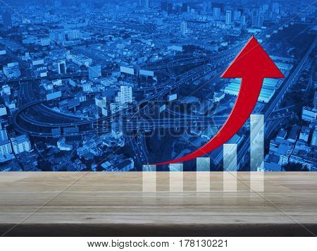 Red arrow with graph on wooden table over aerial of modern city tower street and expressway Success business concept