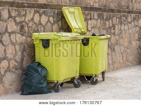 image of green garbage containers near the wall