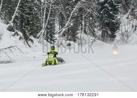 Two snowmobiles go on ice of the frozen river