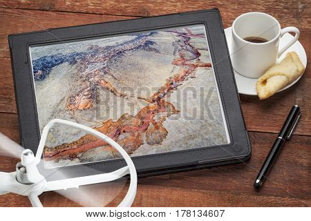 aerial photography concept - reviewing pictures of Colorado foothills with a dry stream on a digital tablet with a drone rotor and coffee, screen picture copyright by the photographer
