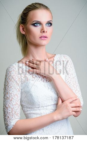 Studio fashion shot: a lovely young girl in white dress