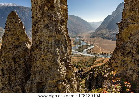 A picturesque autumn top view with high rocks in the form of stone mushrooms on a background of mountains a valley with a winding river and a blue sky