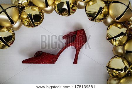 A golden christmas bell wreath with a sparkly glitter red shoe bauble