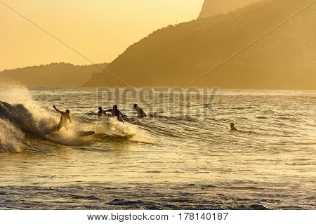 Surfing during the summer sunset at Ipanema beach in Rio de Janeiro
