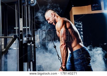 Muscular man working out in gym doing exercises at triceps, strong male naked torso abs. Smoke on background poster