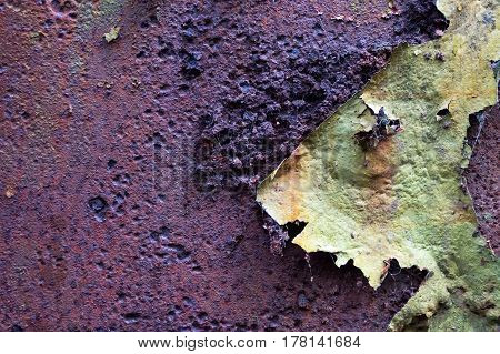 Rusty bumpy brown and purple textured background with green peeling paint with space for text.