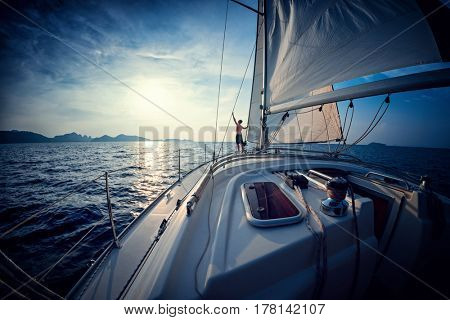 Young man stands on the yacht in the sea at sunset