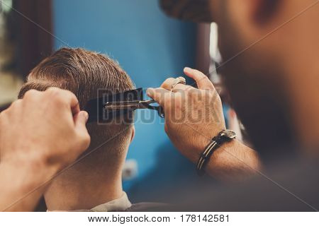 Barber make haircut with scissors in barbershop, closeup of client's head. Hairstyle in male hair salon