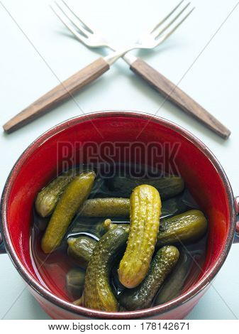 Gherkins in a rustic red ceramic bowl on a modern kitchen table vintage color toned