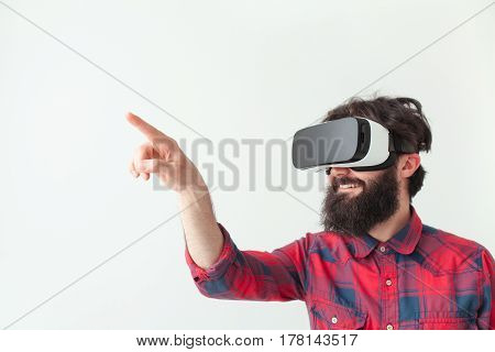 Young man touching the air during the virtual reality game on the white background.