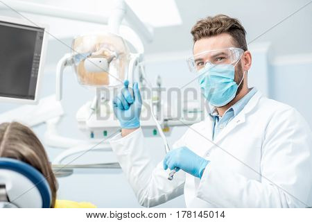 Portrait of a dentist in mask and protective glasses during the dental surgery