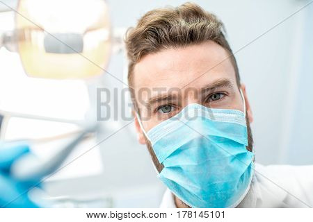 Portrait of scary dentist in mask with dental tools during the surgery looking at camera