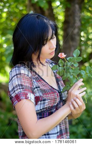 Young brunette woman in a plaid dress holding a small rose in the garden in the summer