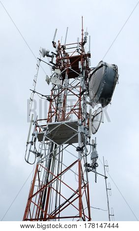 Communication antenna tower with gray sky background