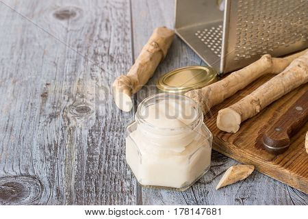 The root of horseradish, a metal grater, a knife and a jar with  seasoning on old wooden table.