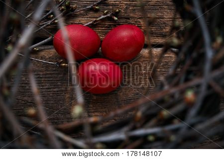 Three Easter eggs on an old wooden table a view through the spring branches