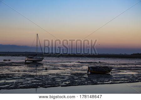 Boats in the muddy sea as dawn breaks