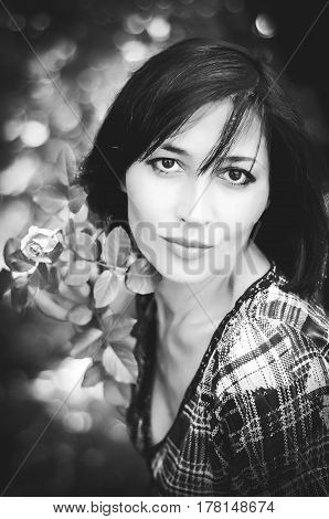 Black and white portrait of young brunette woman in a plain gingham dress holding a small rose in the garden in the summer