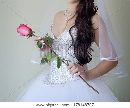 Bride in wedding dress holds a delicate long pink rose