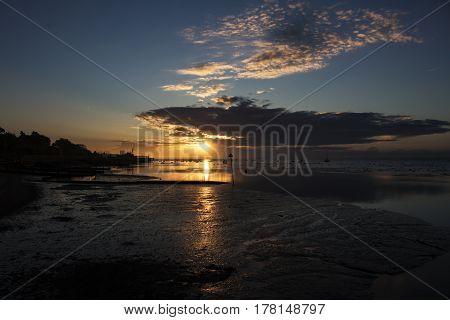 The sun rising along the beach at dawn