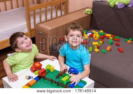 Two little caucasian friends playing with lots of colorful plastic blocks indoor. Active kid boys siblings having fun with building and creating together.