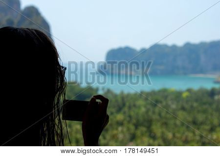 A Young woman taking a photo from a high viewpoint over looking Railay Beach South Thailand.