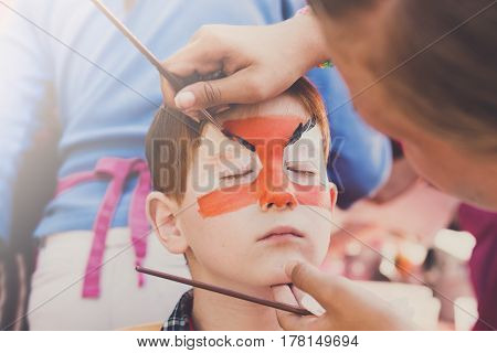 Children holiday, birthday party entertainment. Face art, tiger painting on boy's face