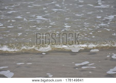 The small waves of the sea and the clean sandy beach in the morning light