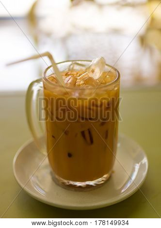 A glass cup of iced Thai tea with ice cubes and a straw on a saucer set in a restaurant.