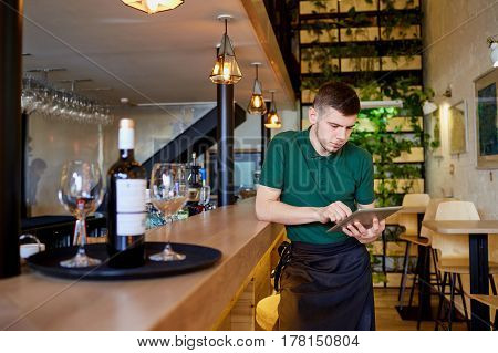 Waiters, bartenders barista rest with the tablet in a break cafe bar restaurant.