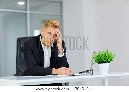 The concept stress crisis depression failure in business. Businessman  holds hand to head  at  table with  laptop I got  office.