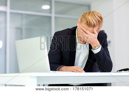 The concept stress crisis depression failure in business. Businessman covered his face with his hand at  table with  laptop I got  office.