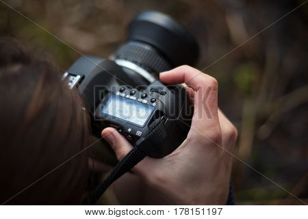 Photographer at work. SLR camera and close-up hands