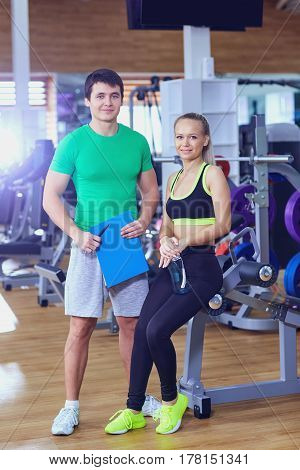 Personal trainer and a woman relaxing in the gym after exercise.