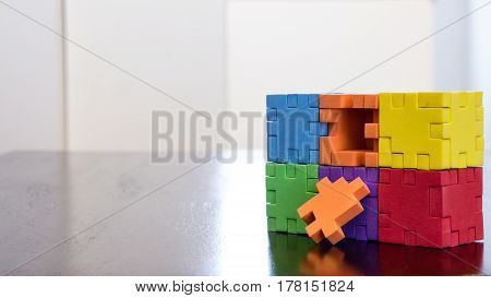 Colorful cube puzzle missing a piece on a table with reflection