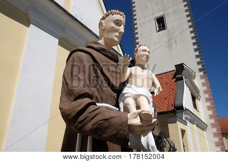 HRVATSKA KOSTAJNICA, CROATIA - JUNE 18: Saint Anthony of Padua statue in front of Parish Church of Saint Nicholas in Hrvatska Kostajnica, Croatia on June 18, 2016.