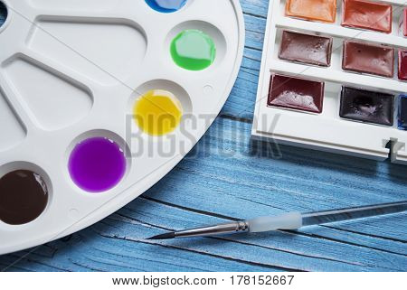 Artist workspace composition with brush palette and watercolor on a blue wooden background. Flat lay