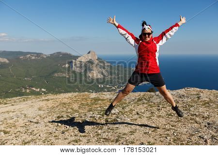 Happy woman jumps on a peak of a mountain in summer time in mountains enjoying the climb with beautiful rocky and sea background outdoors